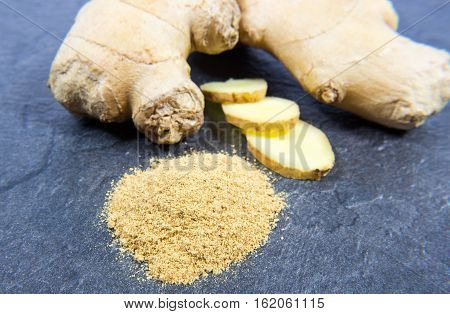 Raw Ginger And Ginger Powder On A Black Background