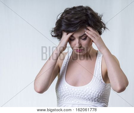 Young pretty brunette girl in white top is looking down and touching her head on white background