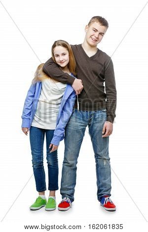 Young boy hugging teenager girl. Brother and sister in casual clothes and jeans. Happy expression. Isolated on white backround. Copy space.
