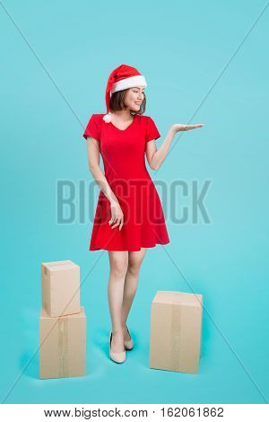 Full-body Of Attractive Cheerful Asian Girl In Santa's Hat Pointing With Her Hand At Copy Space And