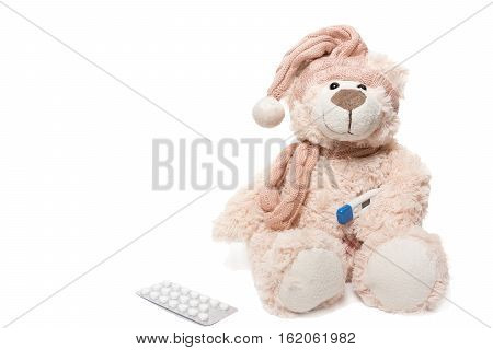 The photo depicts a teddy bear with a thermometer and pills
