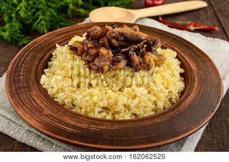 Eastern traditional wheat porridge - bulgur with roasted pieces fatty meats bacon in a clay bowl on dark wooden background.