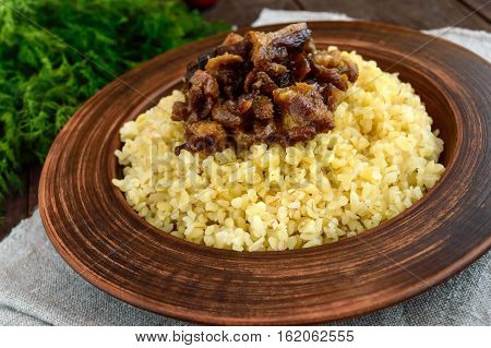 Eastern traditional wheat porridge - bulgur with roasted pieces fatty meats bacon in a clay bowl on dark wooden background. Close up