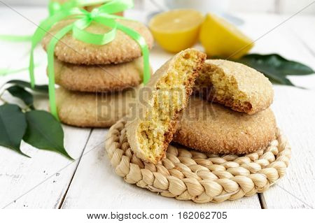 Shortbread lemon flavored cookies: a broken and connected green ribbon for a gift. Fresh lemon on a white wooden background. Close up