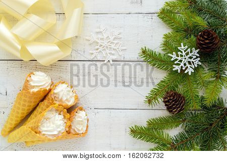 Crispy honey wafers in the form of cones filled with air vanilla cream (ice cream) and green branches of spruce on a white background. The top view. Treats for the party.