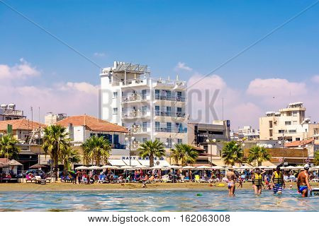 LARNACA CYPRUS - AUGUST 27 2016: Finikoudes Beach with hotels and sunbathers.