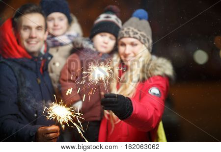 Parents with children with bengal lights in park at night in new year