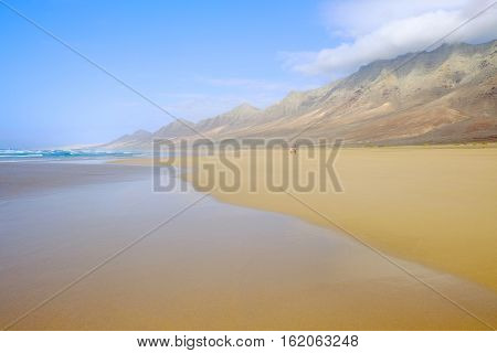 View on the beautiful beach Playa de Cofete with white clouds over the mountains golden sand blue ocean and a couple walking along it. Location the Canary Island Fuerteventura Spain.