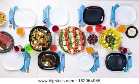 beautifully set table for eight with colorful different dishes and drinks, top view