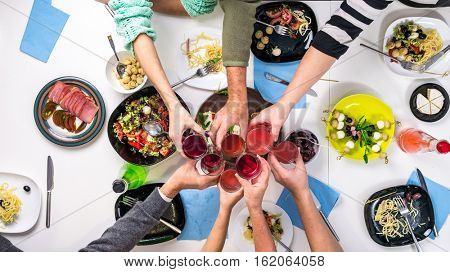 family clanging glasses by the table full of different tasty dishes, top view
