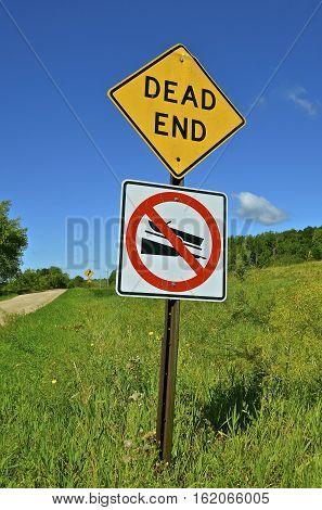 A sign posting a dead end of a gravel road leading to a body of  water lacking a public boat ramp or landing.