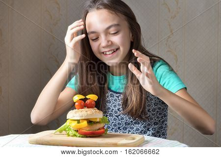 11 year old girl is happy hands up about to eat a hamburger in the form of faces with eyes and cherry tomatoes