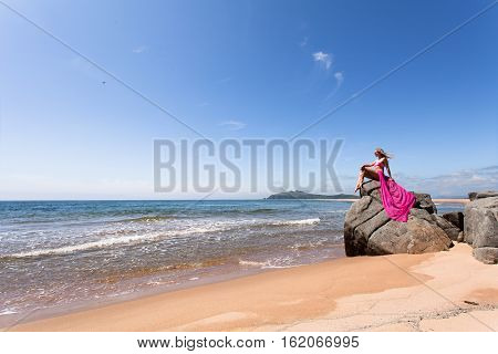 Young slender woman on the sea rocky shore in a pink swimming suit and a pink fabric sitting on the rock.