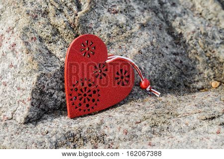 Red wooden heart simbol lying on stone.
