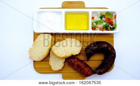 Appetizer With Salt, Olive Oil, Peppers And Onion Cut Into Dice. Accompanied By Bread And Sausage An
