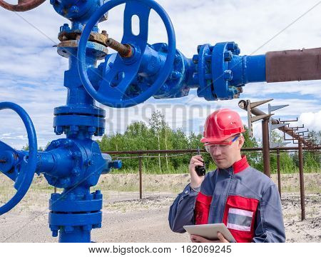 Worker near wellhead valve talking on the radio holding tablet computer and wearing red helmet in the oilfield. Pipeline background. Oil and gas concept.