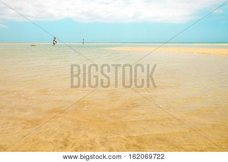 View on the beach Sotavento the lagoon with clear sea water and windsurfers cloudy sky and golden sand. Location Playa de Sotavento Canary Island Fuerteventura Spain.
