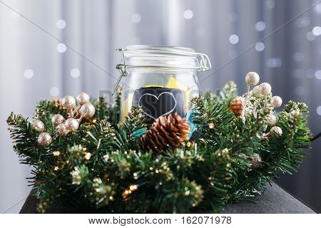jar with stickers with a painted heart behind the Christmas wreath. In the background Christmas lights