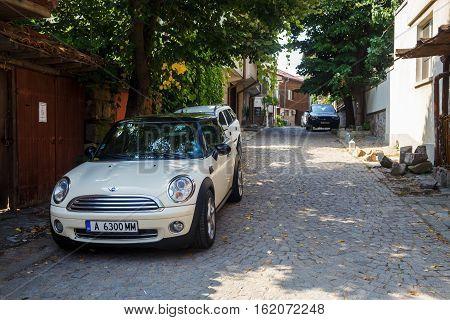 Nesebar Bulgaria - September 03 2014: Mini Cooper car is parked on the narrow cobbled street of the old town of Nessebar Bulgaria.