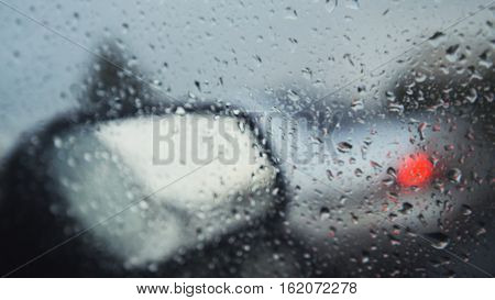 Car glass on a rainy day - defocused background. Moving waterdrops in the wipers of the windshield, close up