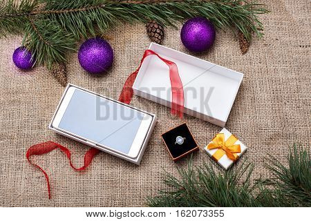 Open Christmas gift boxes with a smartphone and ring among Christmas decorations on a burlap background