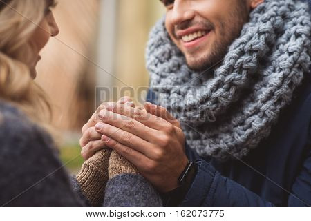 That is real love. Joyful young lovers enjoying time together on date. Man is warming female hands and smiling. They are sitting outdoors in cold weather