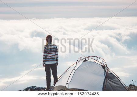 Woman on mountain cliff alone foggy clouds landscape on background Travel Lifestyle concept adventure vacations outdoor tent camping