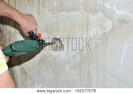 Electric chiseling machine making hole in a concrete wall, with space for copy text