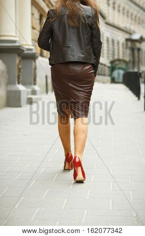 Woman wearing elegant skirt and red high heel shoes in old town. Young beautiful business sexy woman walkingurban background. Back view of a fashion shopper woman legs