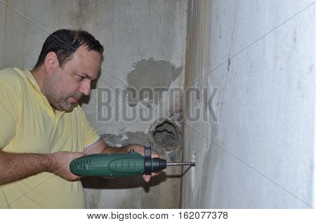 Man holding electric drilling machine and drilling hole in a concrete wall