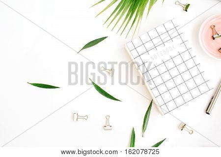 Flat lay top view office table desk. Workspace with notebook palm branch and clips on white background.