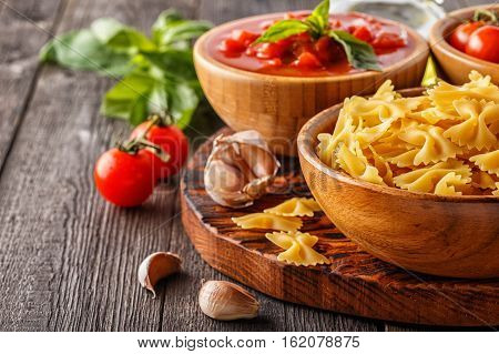 Products for cooking - pasta tomatoes garlic olive oil tomato sauce on the old wooden background.
