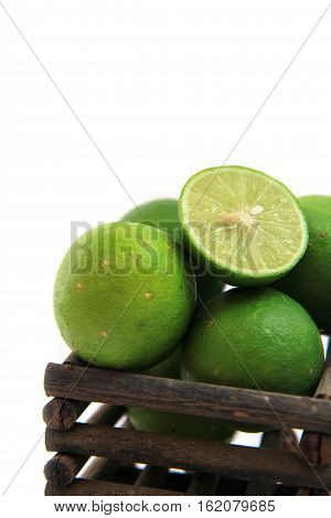 fresh limes in Wooden basket on white background