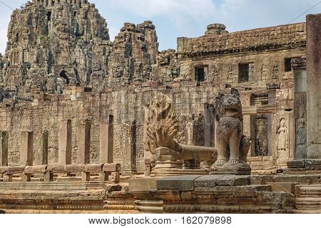 Naga cobra king Vasuki and Lion in the foreground guards Prasat Bayon central temple of Angkor Thom, Siem Reap, Cambodia. Ancient Khmer architecture and famous Cambodian landmark World Heritage.