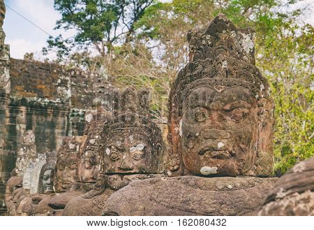 Face of stone giant guarding south gate to Angkor Thom, Cambodia. Magnificent ancient Khmer architecture and famous Cambodian landmark World Heritage.