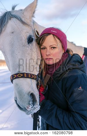 LATVIA, RIGA, DECEMBER, 08, 2016 -  Young beautiful woman petting her big white horse on a winter walk on the first snow in Riga, Latvia