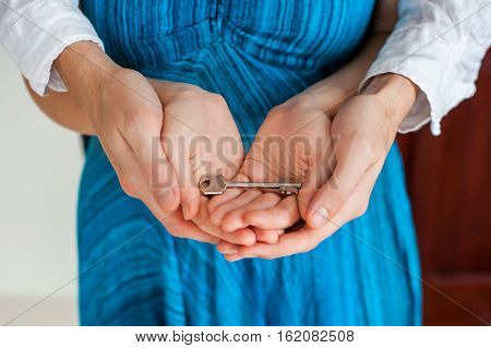 Women's And Man's Hands Hold House Key In The Form Of Heart On The Background Of A Wooden Door. Owni