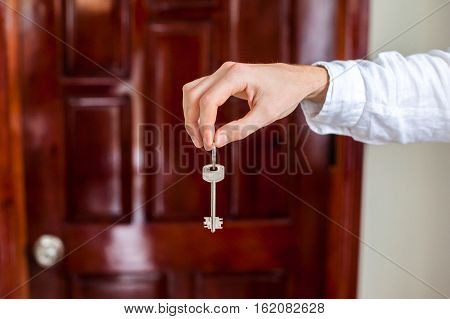 Men's Hands Hold House Key On A Background Of A Wooden Door. Owning Real Estate Concept