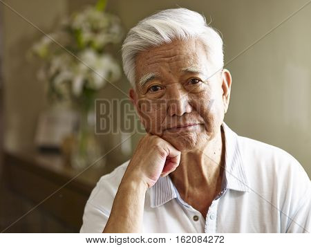 portrait of sad senior asian man hand on chin frontal view.