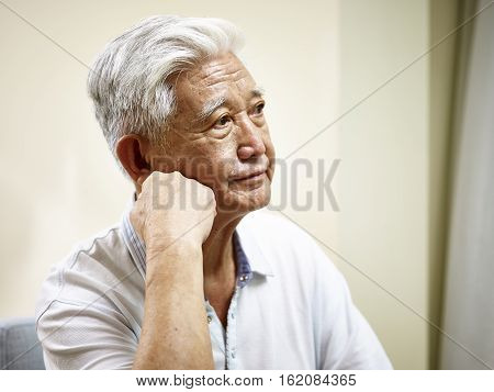 portrait of sad senior asian man hand on chin side view.