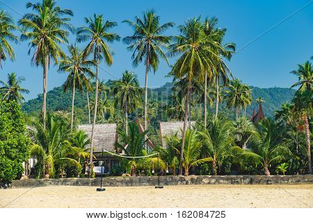 Relaxing on remote paradise beach. Beach volleyball court and coconut palm trees on untouched sandy beach, Koh Chang Thailand