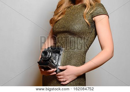 Nice picture of an attractive young woman in evening dress holding a retro camera