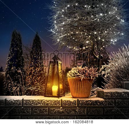 Christmas lantern on snowy stone wall in winter garden