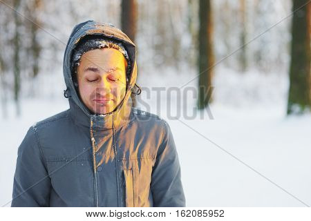Young smiling man with closed from the bright sun through the eyes while walking in winter forest closeup.