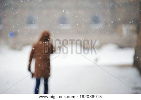 Blurred image of man standing on the street in the yard during snowfall on a cold winter day.