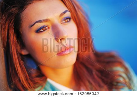 Portrait of young beautiful pensive girl with brown hair in the bright rays of the sunset on blurred background close up.