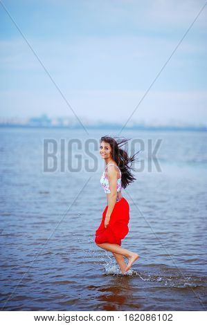 Exciting young long-haired brunette girl in a t-shirt and skirt walks barefoot on the water in the Gulf of Finland in the far blurry background of the building of St. Petersburg