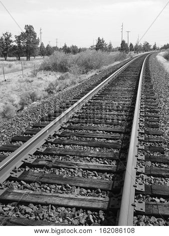 Railroad Tracks disappearing around the bend in Central Oregon on a sunny fall day.