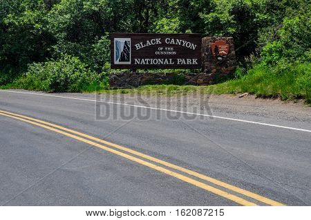 GUNNISON COLORADO: June 28 2015. A wide view across the road from the sign welcoming visitors to the Black Canyon of the Gunnison National Park