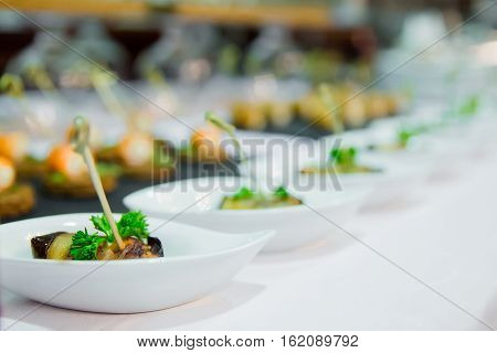 Catering eggplant rolled with cheese in white saucer